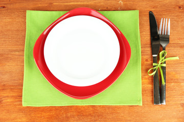 Empty red and white plates with fork and knife