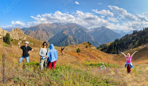 Funny group of people hiking on the meadow of mountain
