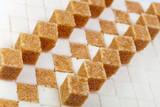 Cubes of not refined reed sugar lie on pieces of white sugar..