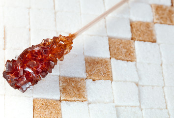 candy brown sugar on a stick lies on lumpy sugar..