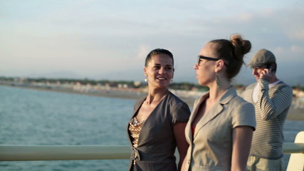 Two happy glamour female friends walking on the pier