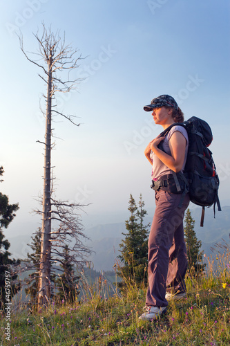 young woman in the mountains at sunset