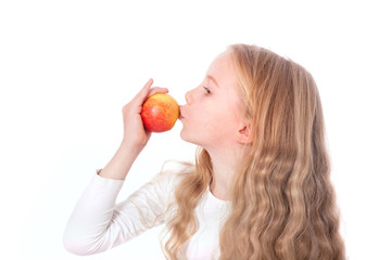 young girl kisses red and yellow apple
