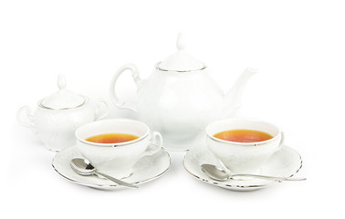 Tea cups, tea pot and sugar on white