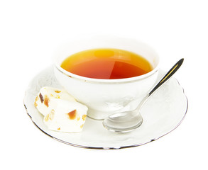 Tea cup with sweets on white background