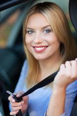 Woman attaching seat belt in car