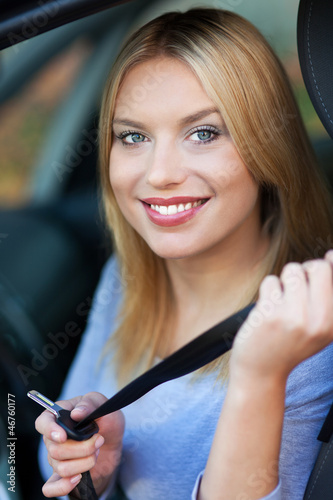 Woman attaching seat belt in car