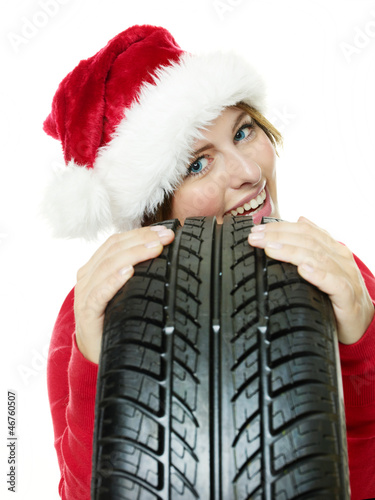 Miss santa leans against a tire waiting for christmas