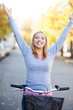 Woman with arms raised while sitting on bike