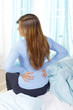 Frau legt die Hände auf den Rücken bei Kreuzschmerzen