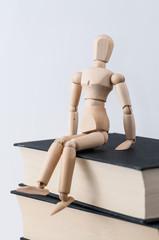 Eine Zeichenpuppe sitzt auf einem Stapel Bücher