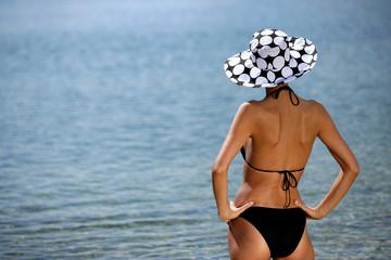 Stunning brunette in bikini looking into the horizon
