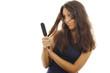 Hübsche Frau schaut entsetzt auf ihre Haarbürste