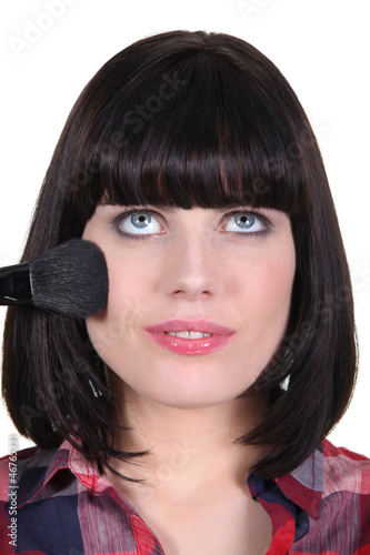 Brunette woman applying makeup