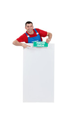 Handyman with wet paint sign pointing at blank poster