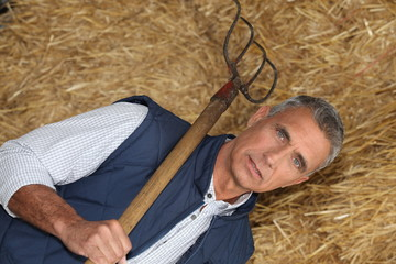 mature handsome farmer posing with fork against hay background