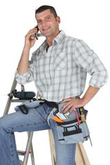 Carpenter posing by ladder