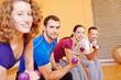 Zufriedene Gruppe mit Hanteln im Fitnesscenter