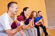 Mann lacht in Fitnesskurs mit Hanteln