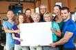 Gruppe hält leeres Schild im Fitnesscenter