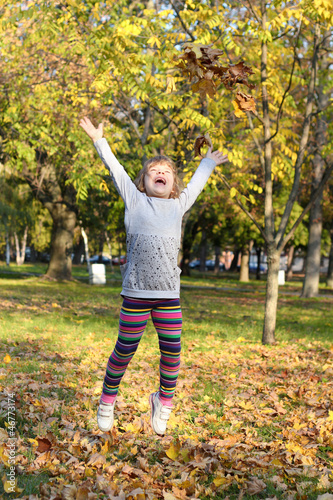 little girl jump and throws leaves
