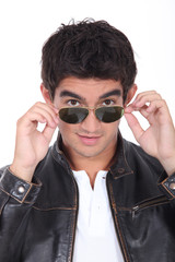 Young man wearing leather jacket and trendy sunglasses