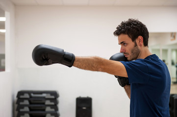 Young man exercising with boxing gloves in a gym.