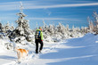 Female hiker walking on snow, winter hiking with dog
