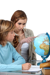 Boy and girl looking at a globe