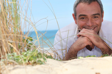 mature man resting at the beach