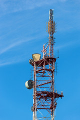 Telecommunication tower with antennas over a blue sky.
