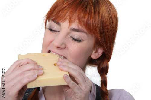 Woman biting into a piece of cheese