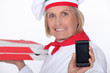 mature female pizza cook showing a cell phone