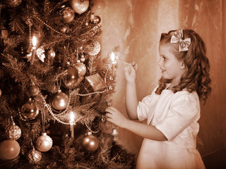 Child ignites candles on Christmas tree.