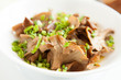 Fried chanterelles with green onions in a white bowl