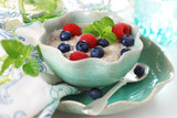 Oatmeal with fresh berries in ceramic dish.