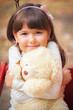 Small beautiful girl and amusing bear