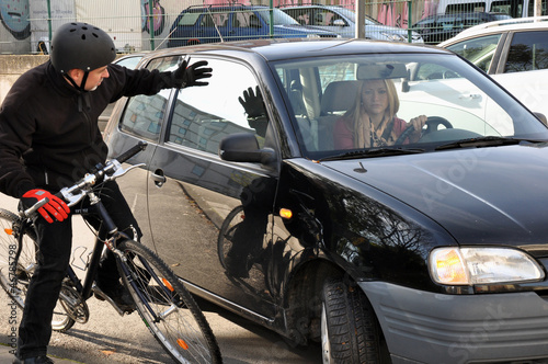 Leinwanddruck Bild Autofahrerin gefährdet Radfahrer