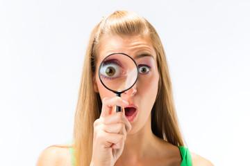Frau schaut durch Lupe oder Vergrößerungsglas