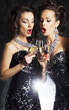 Two beautiful women with champagne singing christmas songs