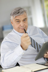Senior businessman talking to client and using tablet