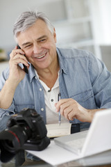 Photographer in office talking to client on the phone