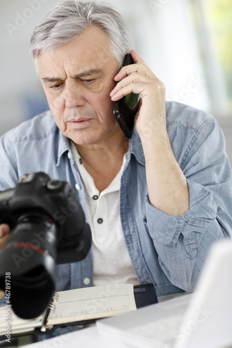 Photographer in office talking on the phone with client
