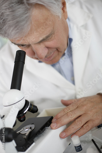 Scientist in lab looking through microscope lens