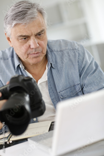 Senior reporter working in office in front of laptop