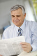 Portrait of senior businessman reading newspaper