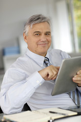 Senior businessman in office using tablet