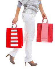 Closeup on woman walking with red shopping bags
