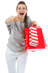 Woman in sweater with shopping bags pointing in camera