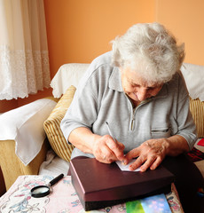 a senior woman writing something on table